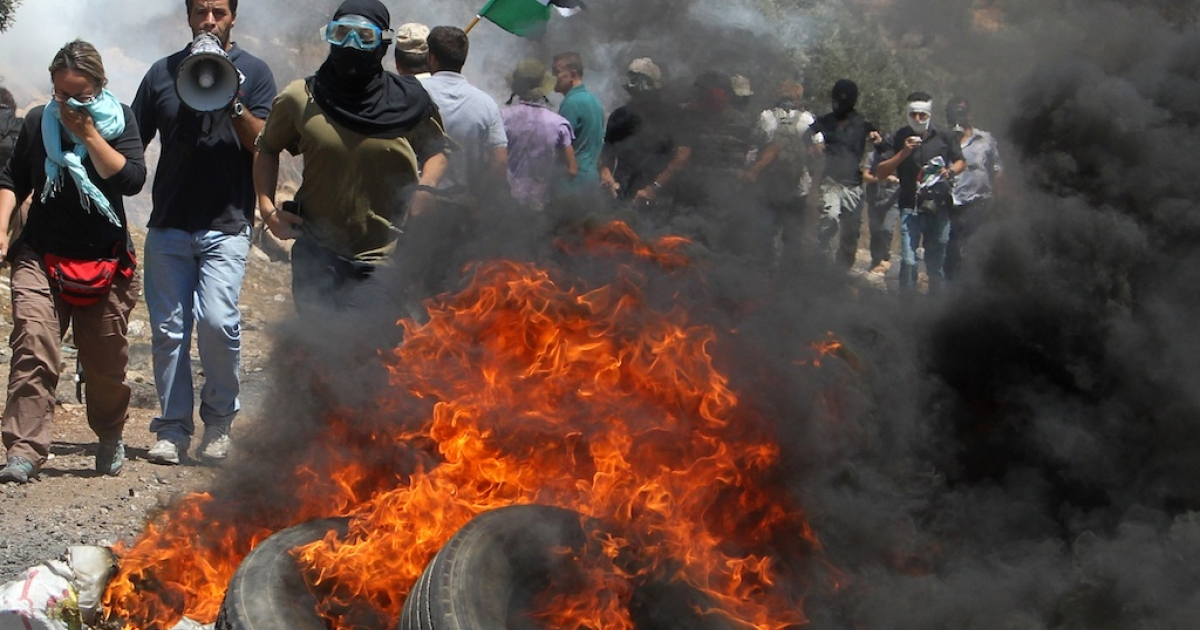 Protesters shout slogans next to a pile of burning tyres during a demonstration against the expropriation of Palestinian land by Israel in the village of Kafr Qaddum, near the West Bank city of Nablus.</p>