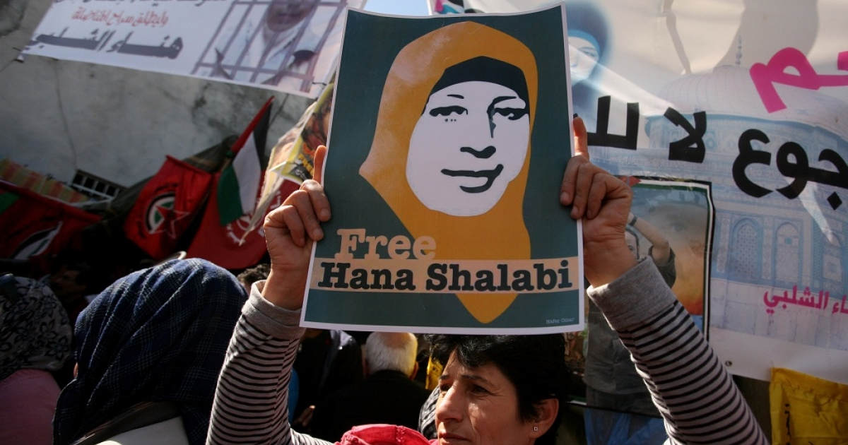 Palestinian women in the West Bank village of Burqin hold up portraits of Hana al-Shalabi during a demonstration demanding her release on Mar. 8 2012, International Women's Day.</p>