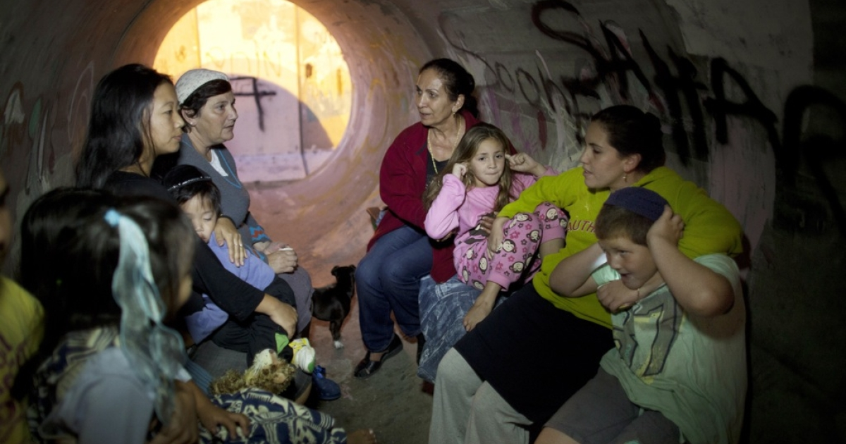 Israelis take cover in a large concrete pipe used as a bomb shelter after a rocket was launched from the Gaza Strip on November 15, 2012 in Nitzan, Israel.</p>
