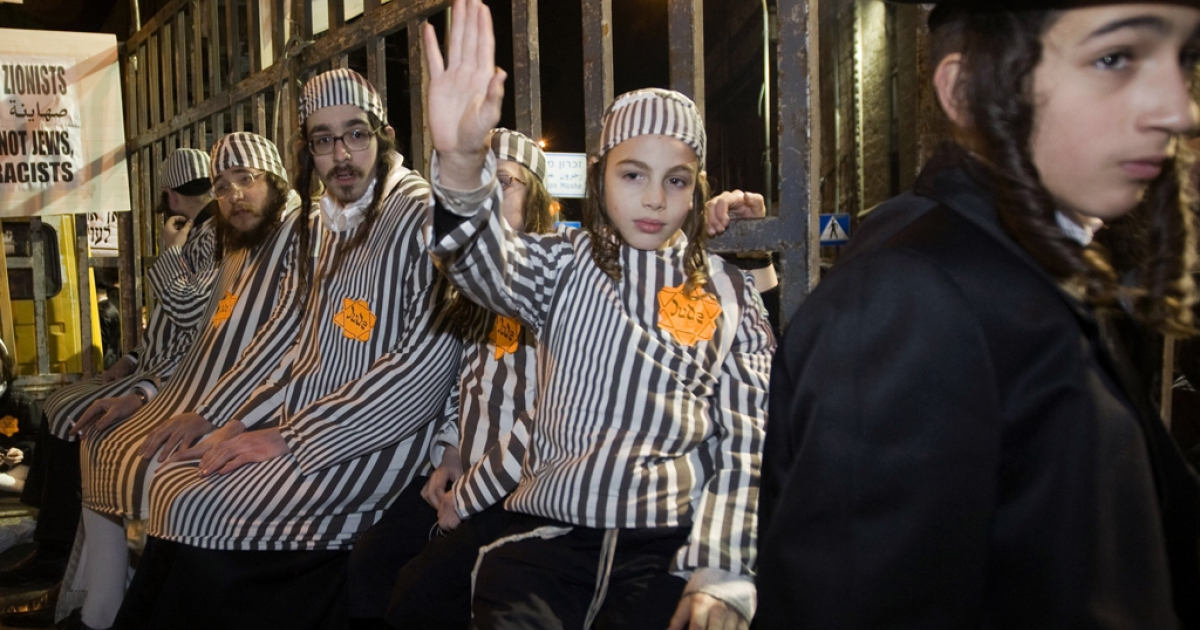 Group of ultra-Orthodox Jews wearing prison uniforms from the Holocaust and yellow Stars of David with 'Jude' written on them sit in a truck with bars during a demonstration in Jerusalem's Mea Shearim neighborhood, on December 31, 2011 to protest against what they call the 'media campaign of incitement' being waged against their community , especially as it refers to the separation of men and women in the ultra-Orthodox Jewish society. AFP PHOTO /AHMAD GHARABLI (Photo credit should read AHMAD GHARABLI/AFP/Getty Images)</p>