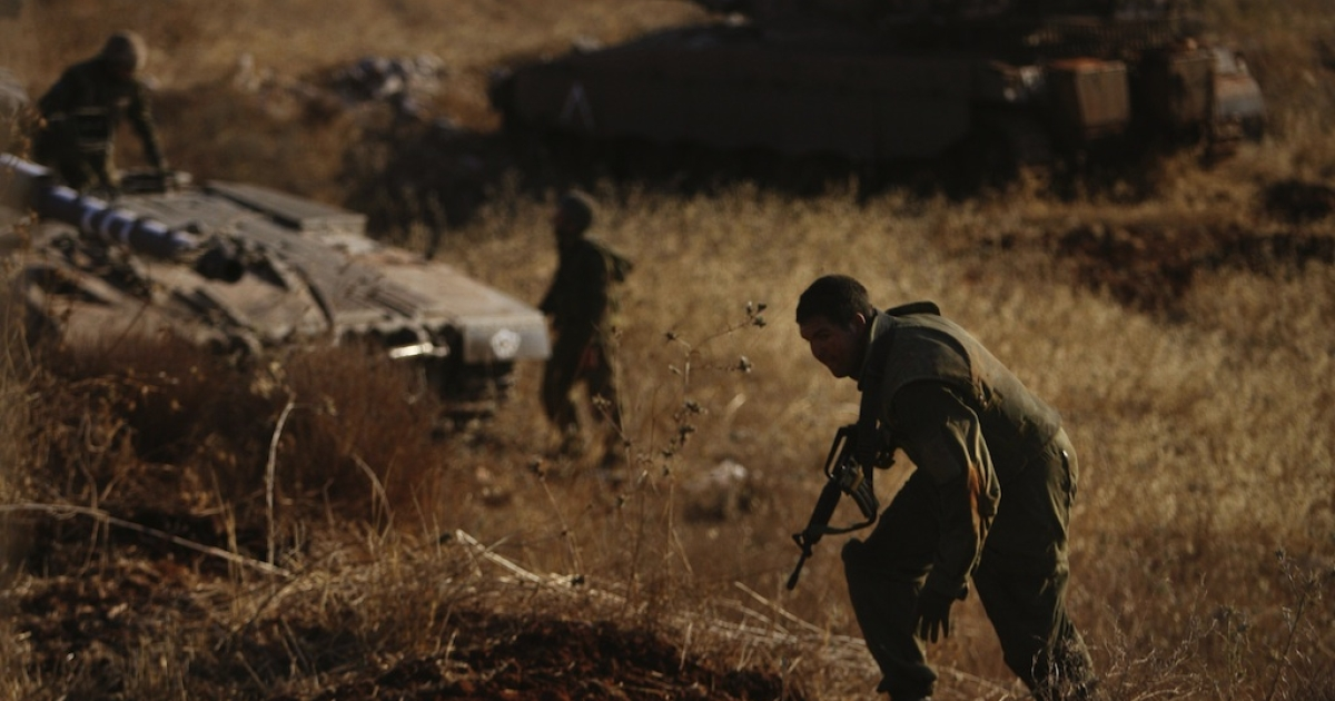 An Israeli soldier ducks as he runs for cover.</p>