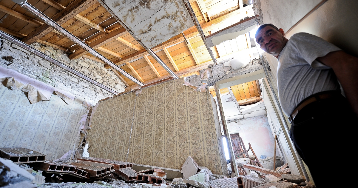 Enzo Federici, a resident of Bazzano, a suburb of L'Aquila hit hard by the quake, stands in his destroyed house on April 2, 2012 in L'Aquila.</p>
