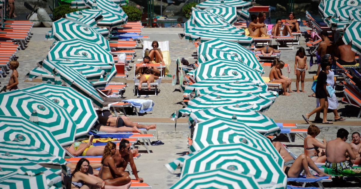 Vacationers sunbath at a private beach near Santa Margherita Ligure, Italy, on Aug. 11, 2011.</p>