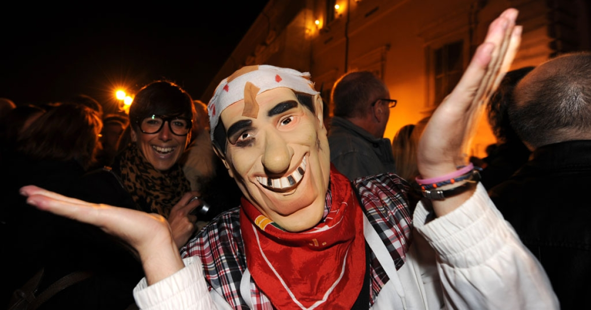 A man wears a Berlusconi mask in front of The Quirinale, the presidential palace in Rome, after Berlusconi resigned on Nov. 12, 2011.</p>