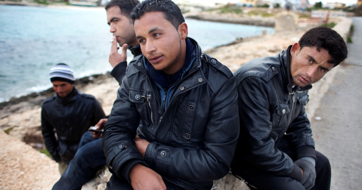 Four Tunisian men wait by the shore of Lampedusa Island, in Italy, for friends they expected a day earlier. Later, they learned that the boat had turned back when the sea became too dangerous to navigate. Some experts say that as many as one-third of immigrants crossing to Europe drown en route.</p>