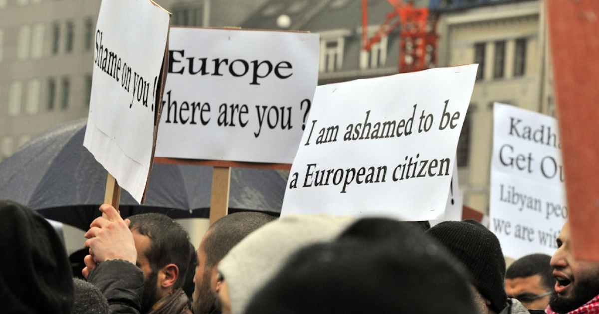 About 50 Libyan residents of Belgium and their supporters hold posters and shout slogans against Libyan leader Muammar Gaddafi during a rally in front of European Union headquarters in Brussels on Feb 23, 2011.</p>
