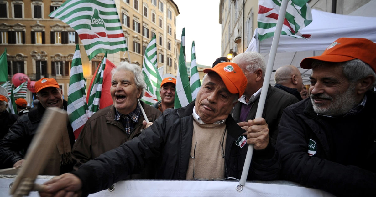Demonstrators hold flags of trade-unions in front of the Italian parliament during a three-hour strike in protest against a draconian austerity plan of the government on December 12, 2011 in Rome.</p>
