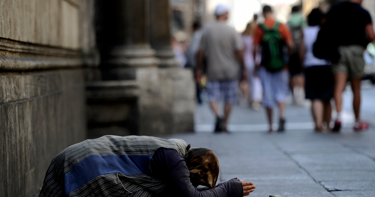 Tourist pass by a street beggar in central Rome on July 11, 2011. Economist Mark Weisbrot argues that right wing euro zone policies serve the rich at the expense of everyone else.</p>