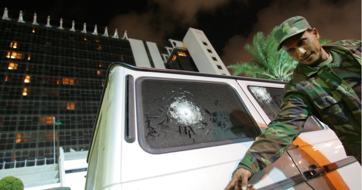 A security guard points at bullet impacts on the vehicle of Italy's consul to Benghazi, on January 12, 2013, in front of the Tibesti hotel in Benghazi. Italy's consul to Benghazi in eastern Libya escaped unscathed after an attack on his bullet-proof car in the city on January 12, Italian news agency ANSA reported, quoting local security sources. The car in which the consul, Guido De Sanctis, was travelling was shot at but no one was injured, the report said.</p>