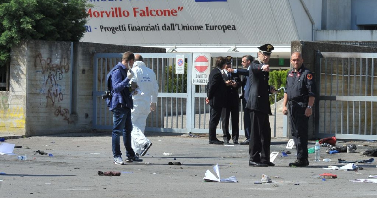 Policemen search for evidence after the blast near a school in Brindisi, southern Italy, on May 19, 2012.</p>