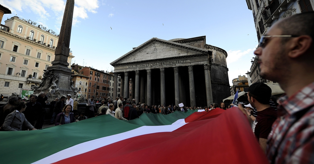 Protesters hold an Italian flag in front of Rome's Pantheon during a protest against the vote at the parliament for approving a measure that challenges the right of a Milan court to hold a sex crime trial against Italian Prime Minister Silvio Berlusconi on April 5, 2011. The vote is not binding and the Constitutional Court will have a final say on whether the court in Milan has the right to try Berlusconi or whether the case should be heard by another body like the special court for ministers.</p>