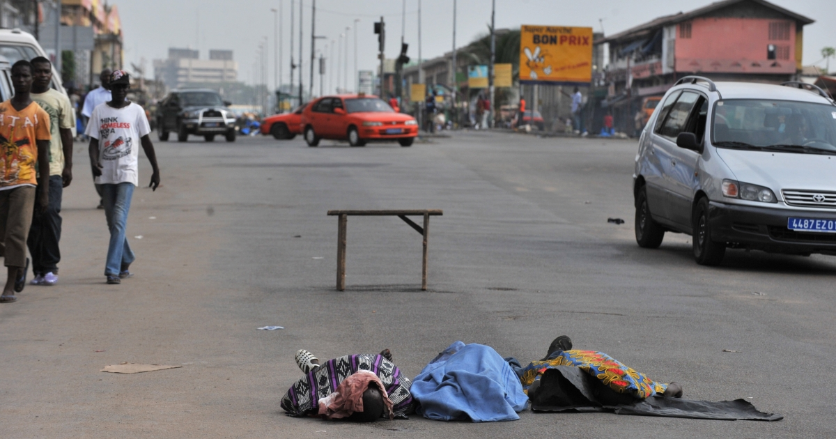 Residents walk on March 18, 2011 past the bodies of three men killed the day before in a street of the popular Abidjan district of Adjame, Ivory Coast.</p>