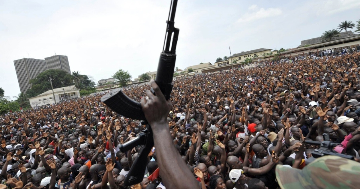 A soldier in the Ivory Coast Army brandishes his gun in front of thousands of young supporters of Ivorian strongman Laurent Gbagbo. The young men gathered to enroll in the Ivorian army, on March 21, 2011 in Abidjan. Fervent backers of Gbagbo streamed to enlist in his armed forces as the United Nations faced pressure to do more to protect civilians in post-election bloodshed in which more than 400 people have been killed. Gbagbo, who refuses to cede power after disputed November polls, is seeking to boost his army and quash efforts by fighters backing internationally recognized president Alassane Ouattara to seize the economic capital Abidjdan.</p>