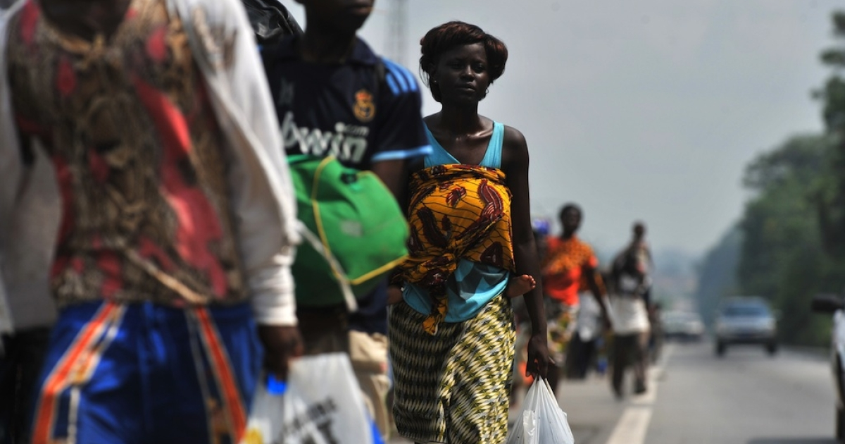 Residents carrying their luggage flee the neighborhood of Abobo PK 18, a suburb of Abidjan, on Feb. 24, 2011.</p>