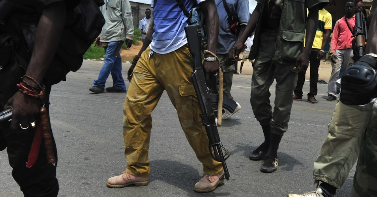 Armed militiaman backing internationally recognized president Alassane Ouattara walk at a makeshift checkpoint on March 24, 2011, in the Abobo district of Abidjan.</p>