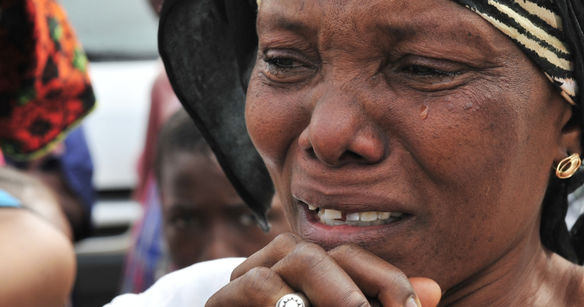 A woman cries as a body is exhumed from a grave in the Ivory Coast on January 25, 2012.  Ivory Coast justice officials exhumed the body in an investigation of mass graves that may contain victims of 2010-2011 post election violence.</p>