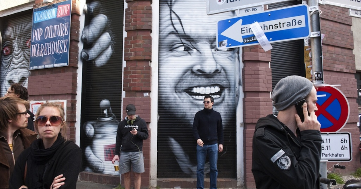 Revelers hang out in front of a closed store featuring a portrait of US actor Jack Nicholson in the film 'The Shining' during a May Day street festival in Berlin's Kreuzberg district May 1, 2011.</p>