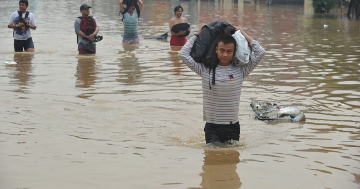 People wade through a flooded street in Jakarta.</p>