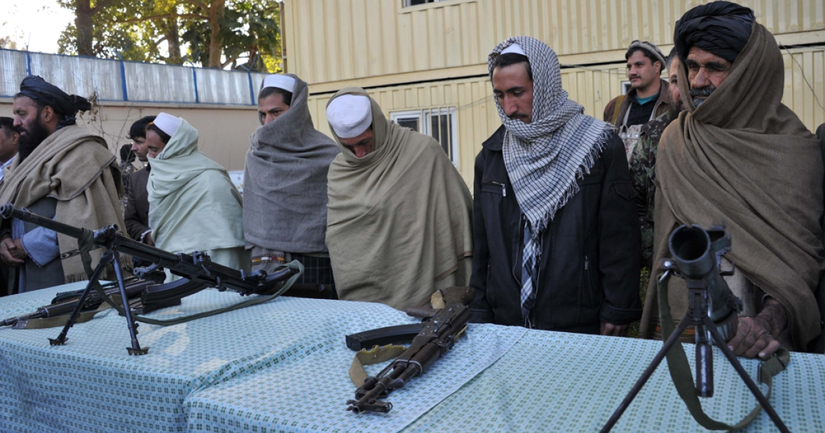 Former Taliban fighters stand next to their weapons as they join a peace and reconciliation process at a ceremony in Jalalabad, Afghanistan, on Jan. 13, 2013. As the capital of Nangarhar province, Jalalabad is one of the most important economic and political centers in the eastern part of the country.</p>