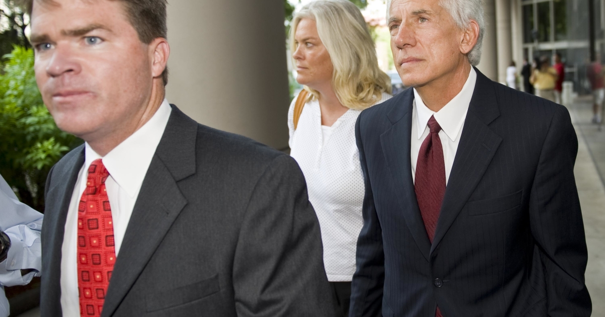 Former Stanford International Bank Ltd. CFO James Davis (R) leaves the Bob Casey US Courthouse in Houston, Texas, with his wife (C) and his attorney David Finn (L) after his arraignment on July 13, 2009.</p>