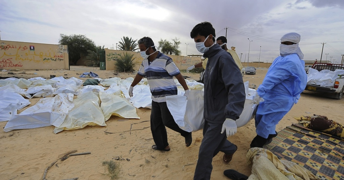 Libyans carry a body bag containing the remains of a loyalist fighter believed to have been killed in a NATO bombing before the capture of Muammar Gaddafi in the Libyan town of Sirte on Oct. 22, 2011.</p>