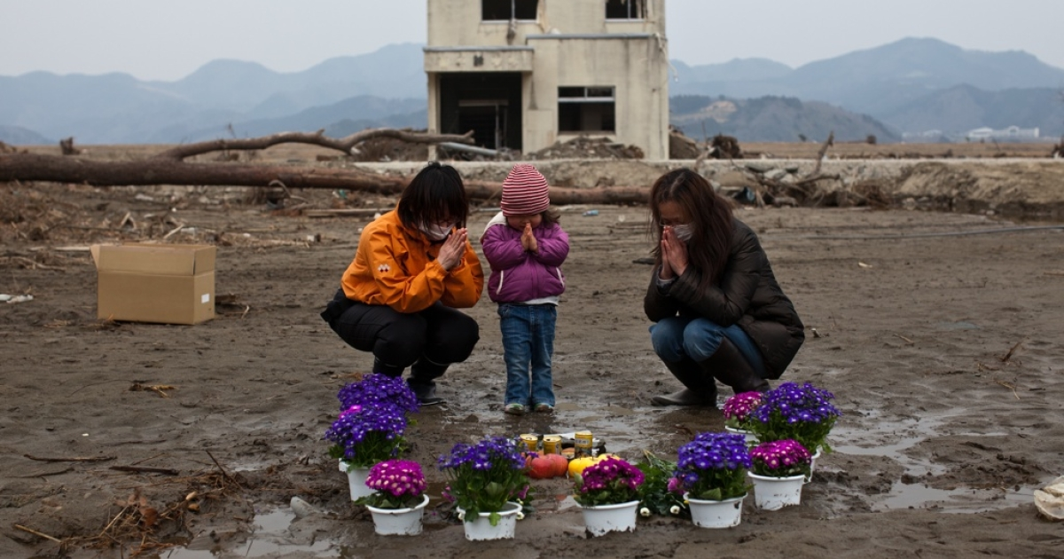 A month after the earthquake and tsunami struck Japan, 2-year-old Ayaka and her family prays for her missing grandmother at a vacant lot where they had lived in Ishinomaki, Miyagi prefecture on April 11, 2011.</p>