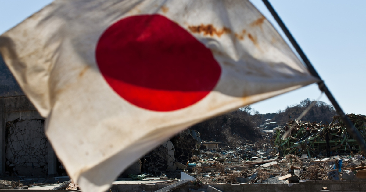 A Japanese flag waves in the wind amid the wreckage and devastation of the March 11 tsunami in the town centre of Onagawa, Miyagi prefecture, on April 6, 2011.</p>