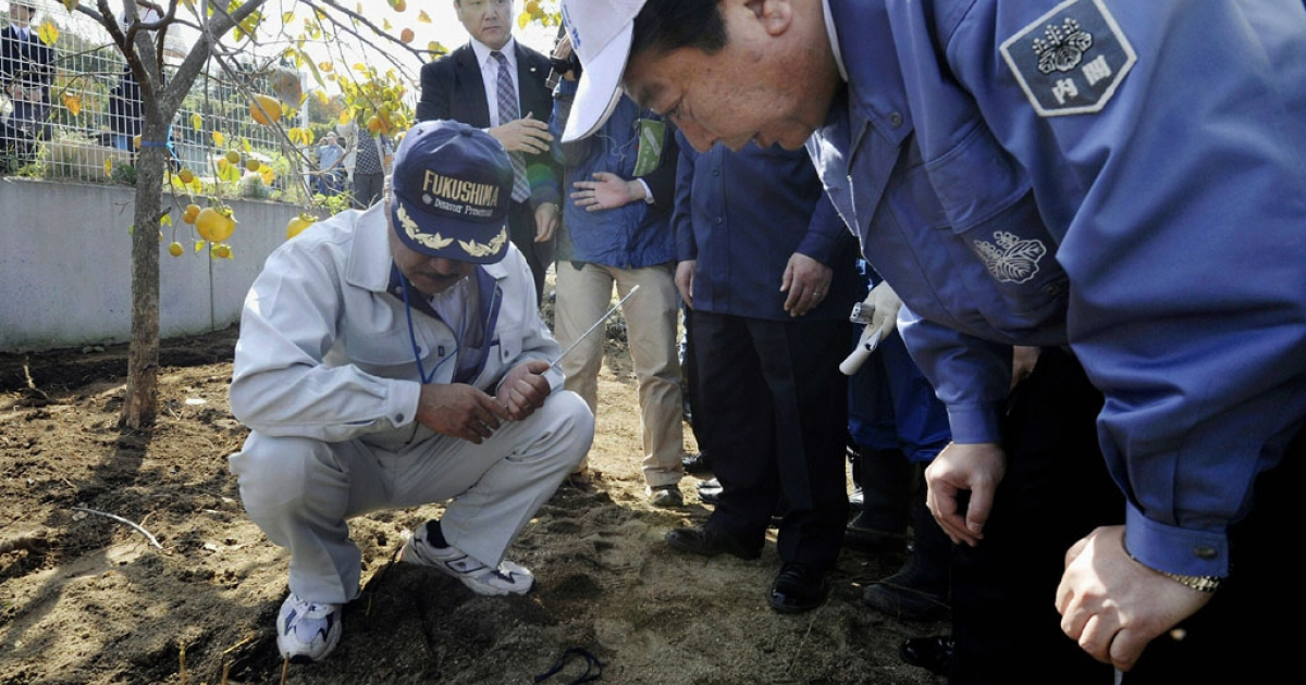 Japanese Prime Minister Yoshihiko Noda looks at radiation being measured in Fukushima City, Fukushima prefecture, Oct. 18, 2011.</p>
