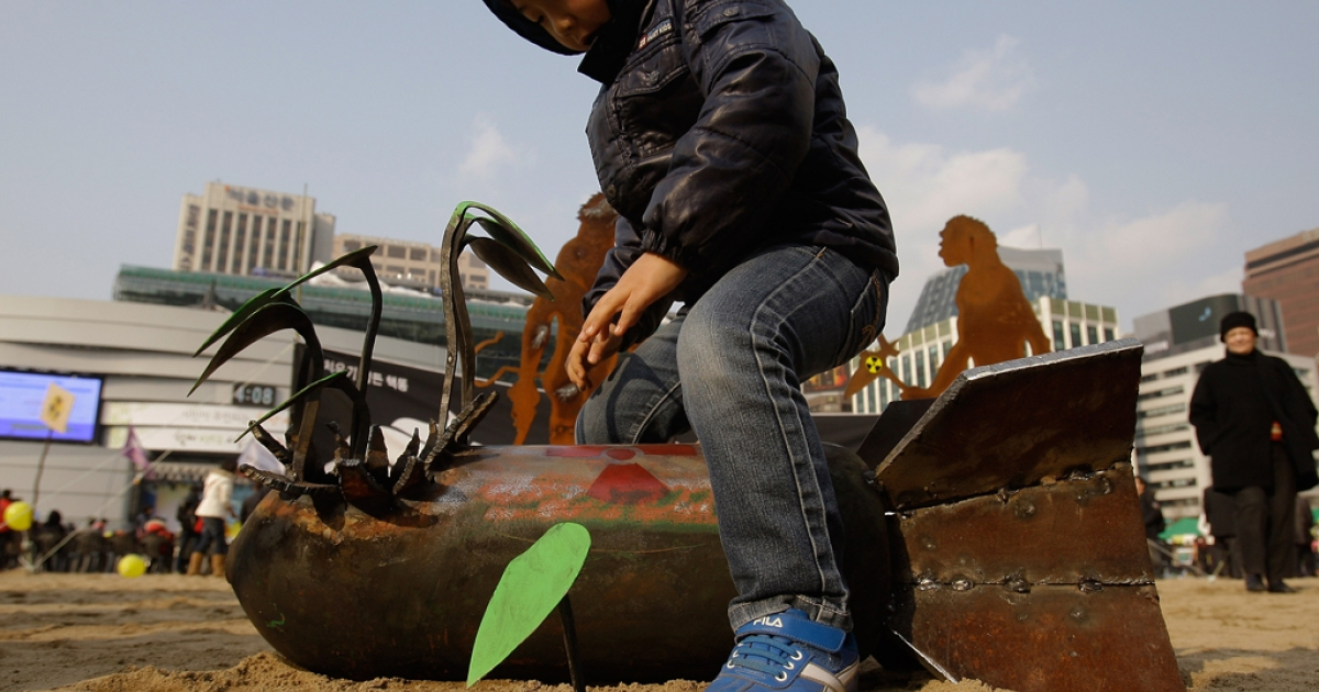A South Korean boy plays with nuclear bomb is exhibits during a rally held to commemorate the Fukushima nuclear disaster on the eve of the one year anniversary of Japan's earthquake and tsunami on March 10, 2012 in Seoul, South Korea.</p>