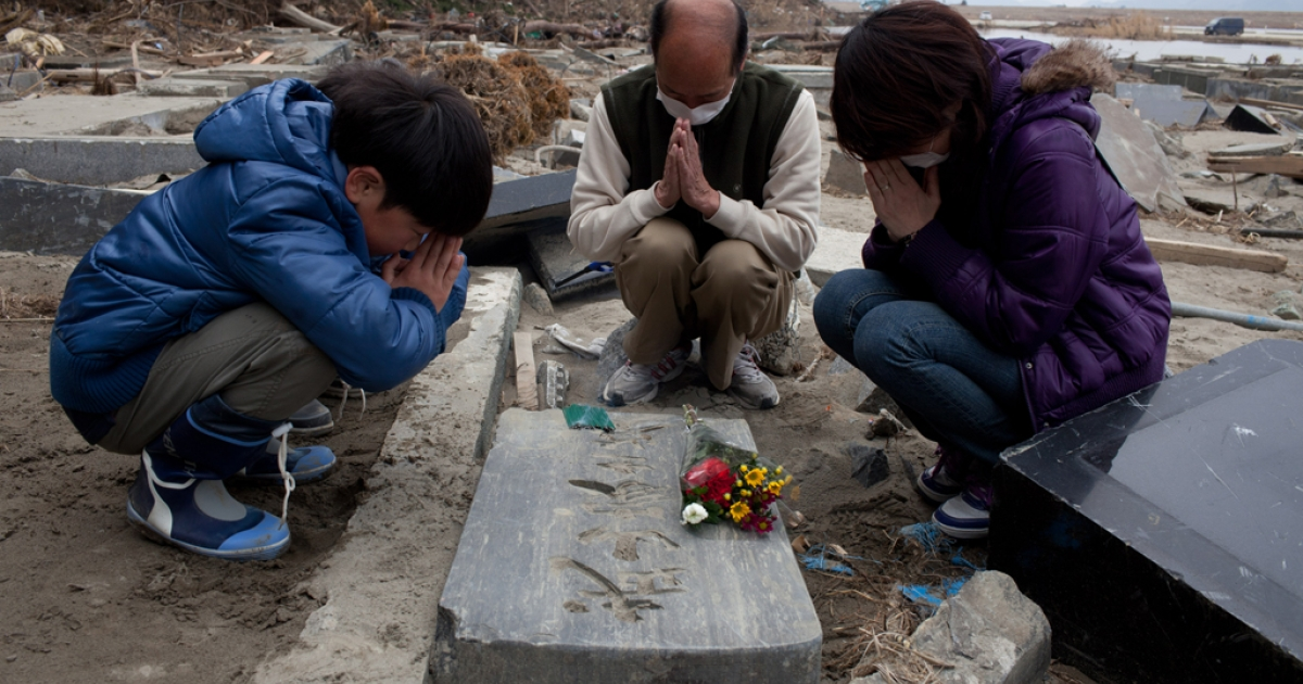 A month after the tsunami devastation, a family prays by a grave in Ishinomaki, Miyagi prefecture on April 11, 2011.</p>