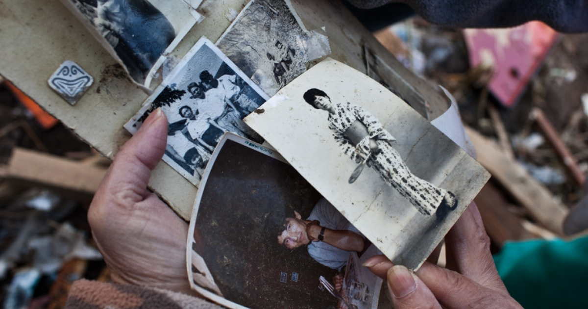 A family member retrieves photographs of her missing grand father and mother's old photos amongst debris in Minamisanriku, Miyagi prefecture, March 28, 2011.</p>