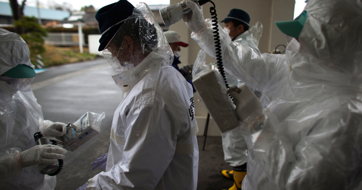 Japanese policemen wearing a protective suits undergo testing for possible nuclear radiation at screening center about 35 kilometers away from Fukushima Nuclear Power Plant as they finish their duty inside exclusion zone on April 9, 2011 in Minamisoma, Fukushima Prefecture, Japan</p>