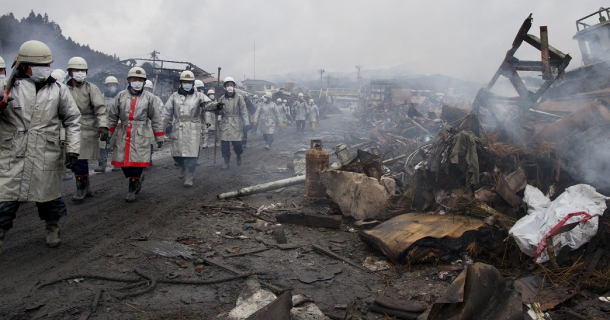 Rescue workers look for bodies on March 16, 2011, amid the rubble of a village destroyed by Friday's devastating earthquake and tsunami in Japan.</p>