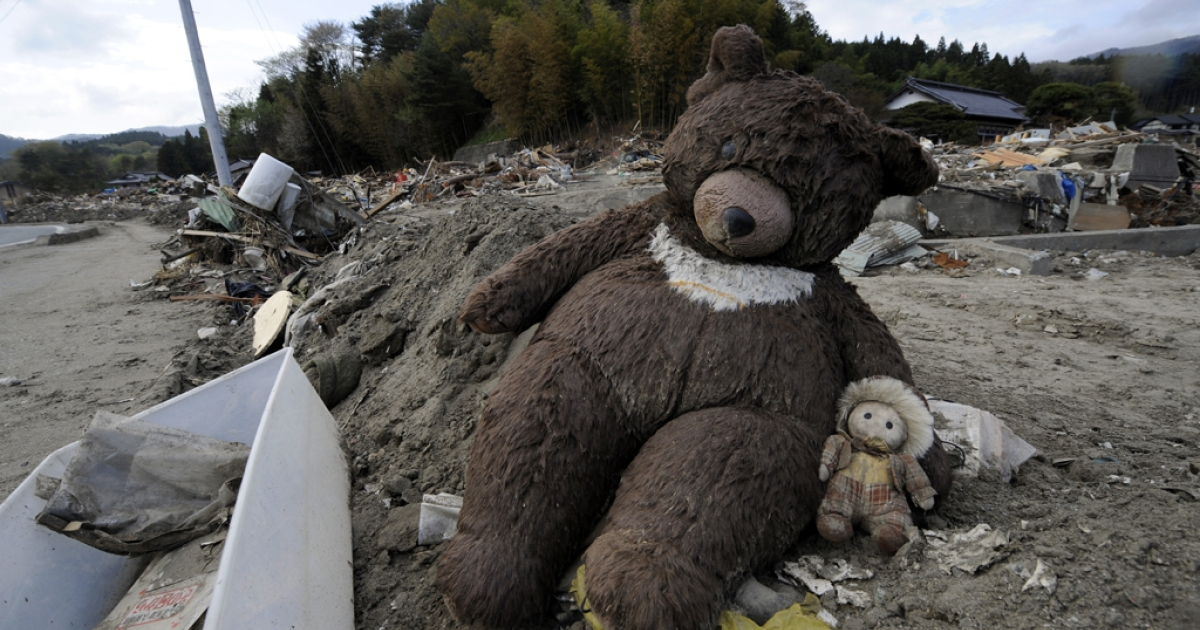 A teddy bear and a doll found in the debris sit at the side of a road in the tsunami-devastated city of Rikuzentakata, Iwate prefecture on May 7, 2011.</p>