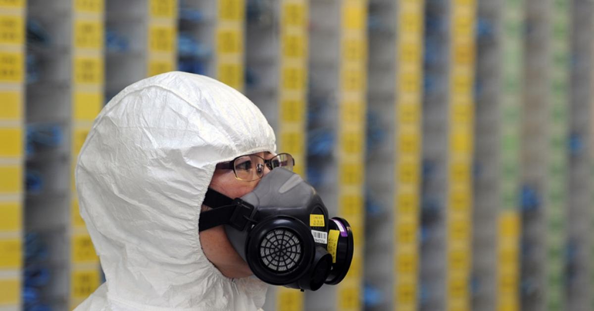 An engineer wears radiation protective gear.</p>