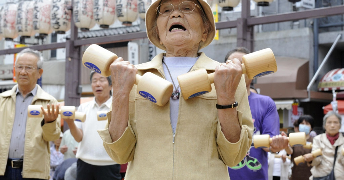 Elderly people work out with wooden dumb-bells in the grounds of a temple in Tokyo.</p>