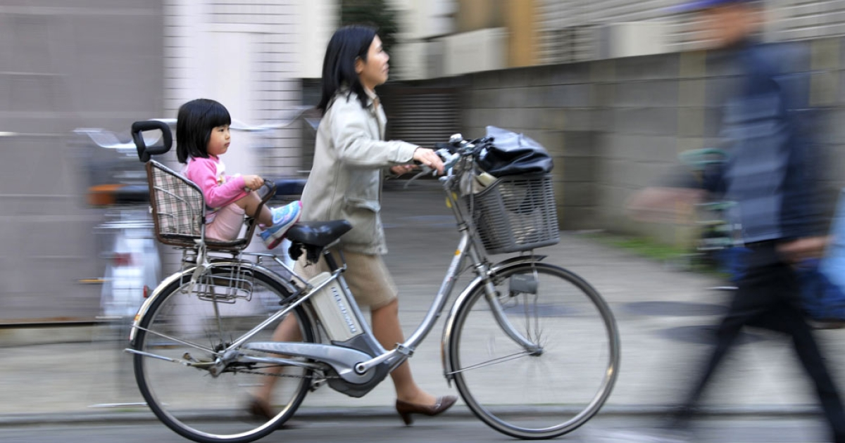 A mother pushes her bicycle carrying her daughter in Tokyo on March 19, 2010.</p>