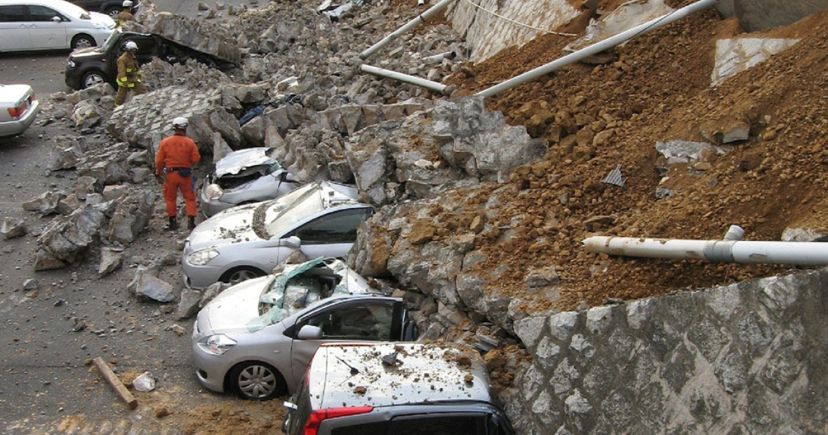 Vehicles are crushed by a collapsed wall at a carpark in Mito city in Ibaraki prefecture on March 11, 2011 after a massive earthquake rocked Japan.</p>
