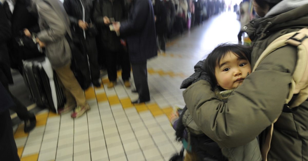 A woman holds a child in a long queue as people rush to get out of the city in Yamagata, Yamagata prefecture on March 15, 2011.</p>