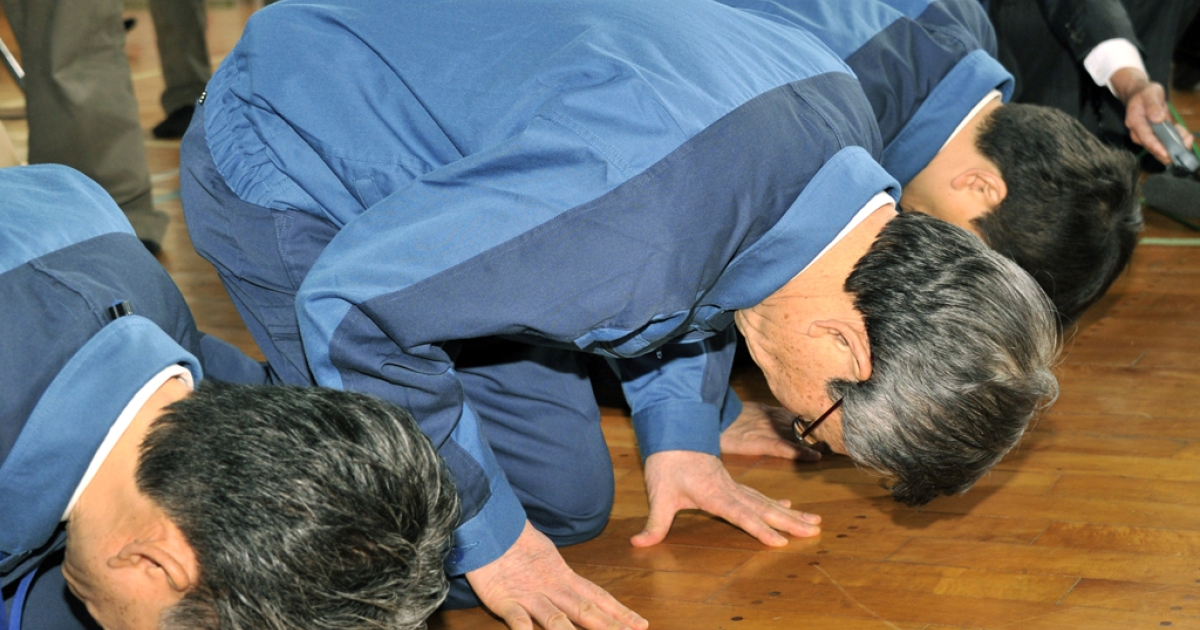 Former TEPCO President Masataka Shimizu (center) and company employees bow to apologize to evacuees from the town of Namie near TEPCO's Fukushima nuclear power plant on May 4, 2011.</p>