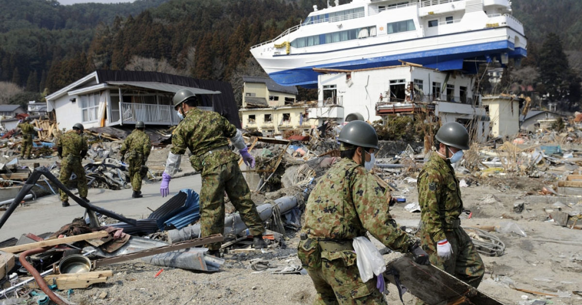 Japanese soldiers search for the missing in the rubble below the Hamayuri, a catamaran signtseeing boat, that was pushed up atop a two-story Japanese inn building by the tsunami at Otsuchi town in Iwate prefecture on March 31, 2011.</p>