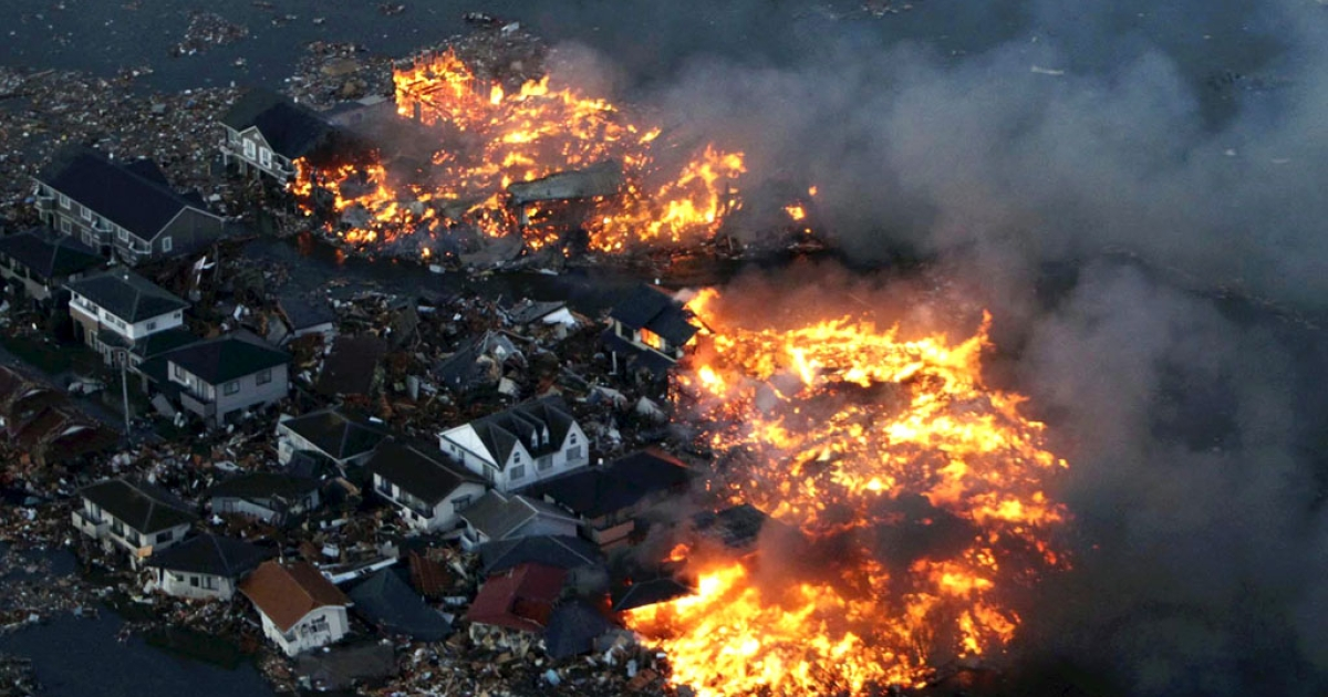 This aerial shot shows houses in flame after being hit by a tsunami at Natori city in Miyagi prefecture, northern Japan on March 11, 2011.</p>