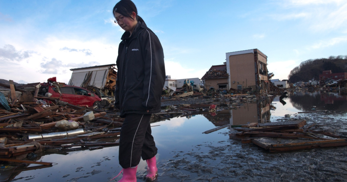A Japanese girl stands amongst the rubble where her home had been, while visiting it for the first time on March 18, 2011 in Kesennuma, Japan.</p>