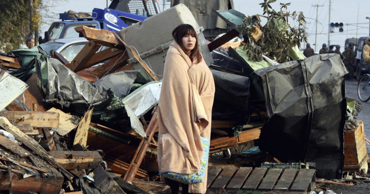 A girl, wrapped in a blanket, stands to look on tsunami damaged town at Ishinomaki city in Miyagi prefecture on March 13, 2011.</p>