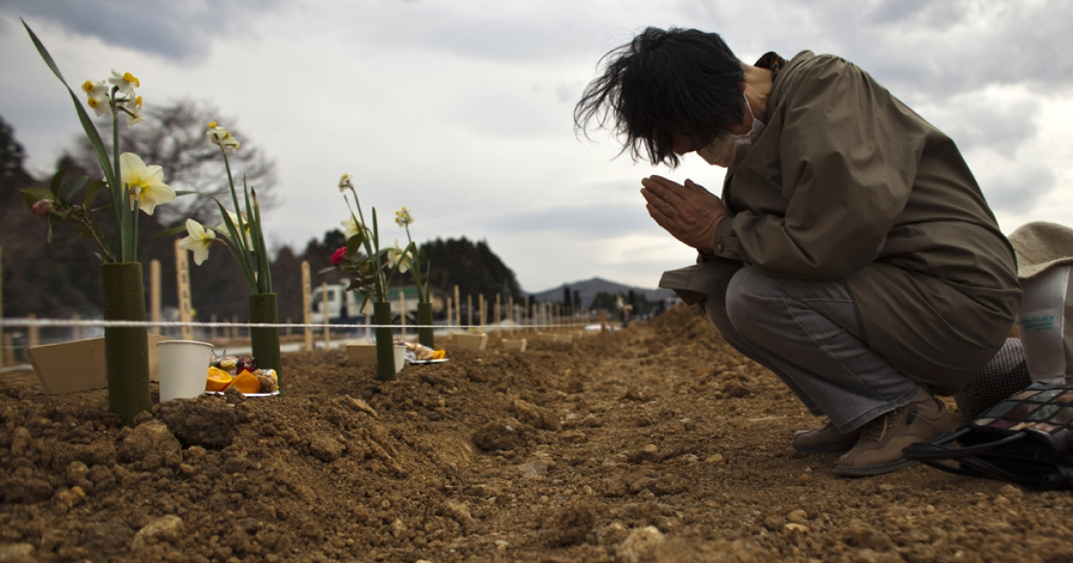 A relative pays her respects to an earthquake victim in Yamamoto, Miyagi Prefecture, Japan.</p>