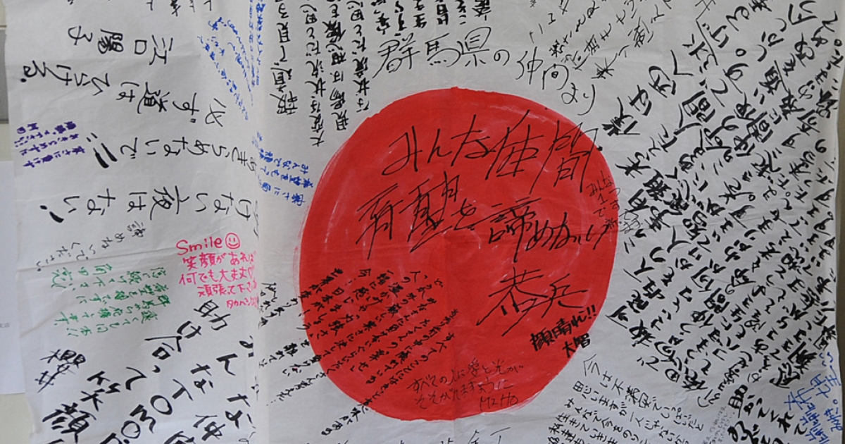 A flag of Japan with messages of hope and strength written by residents is posted at a primary school being used as an evacuation center in Ishinomaki in Miyagi prefecture on March 21, 2011.</p>