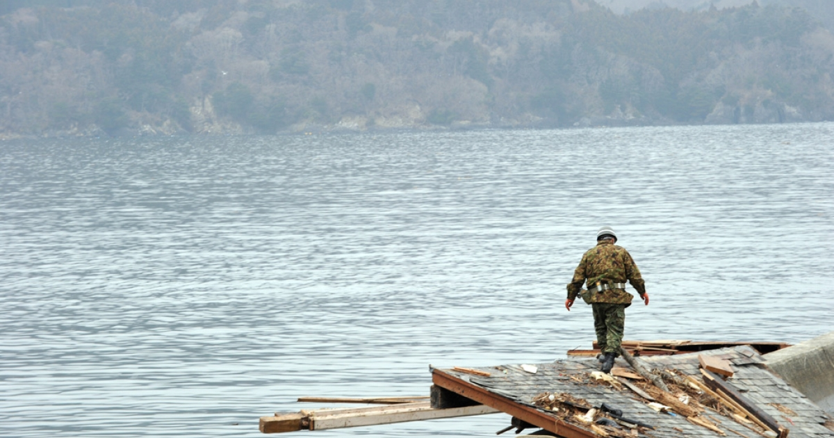 A Japanese Self-Defense Force soldier looks for missing people at a small village beside the Onagawa nuclear plant in Onagawa, Miyagi prefecture, on March 21, 2011.</p>
