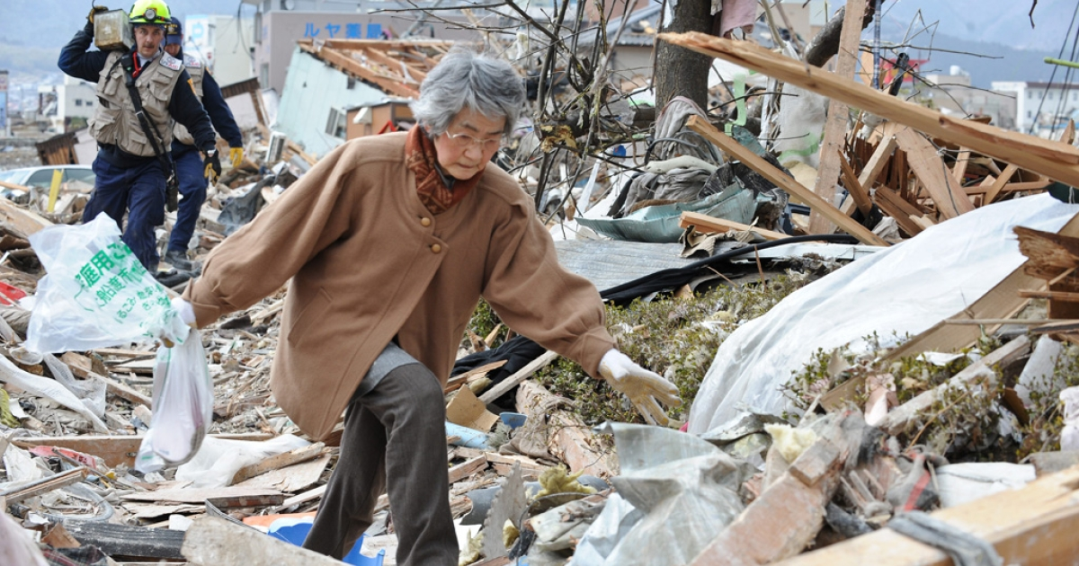An elderly woman walks through the rubble in the devastated city of Ofunato on March 15, 2011.</p>