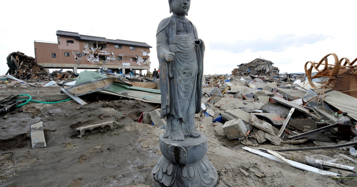 A religious statue stands amongst debris in a tsunami-devastated area close to the sea front, in Natori, Miyagi Prefecture, on March 14, 2011.</p>