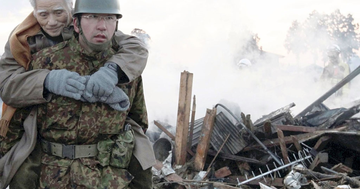 A soldier carries an elderly man on his back to a shelter in Natori city, Miyagi prefecture on March 12, 2011.</p>